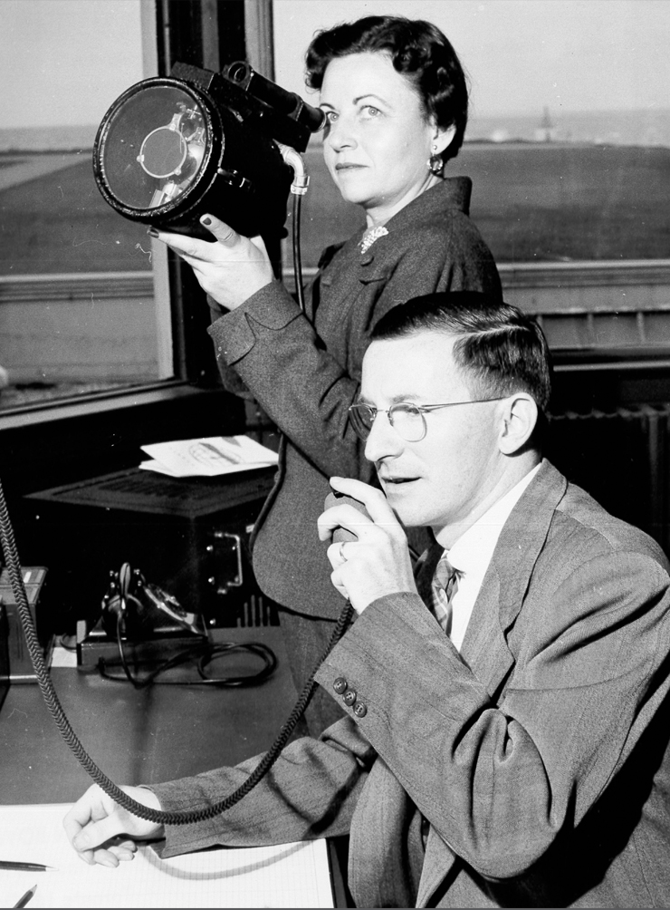 Man on radio with lady in background with air traffic control light