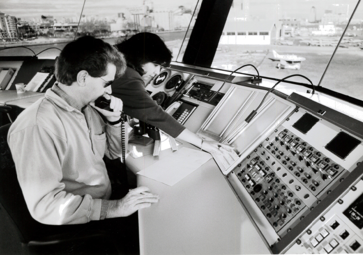 Meteorologists infront of complex panel of switches