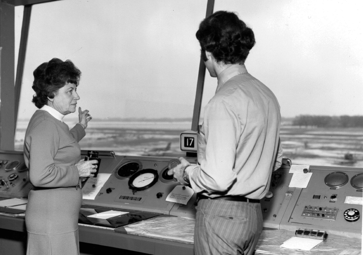 A lady and a gentleman in air traffic control looking out over the runway