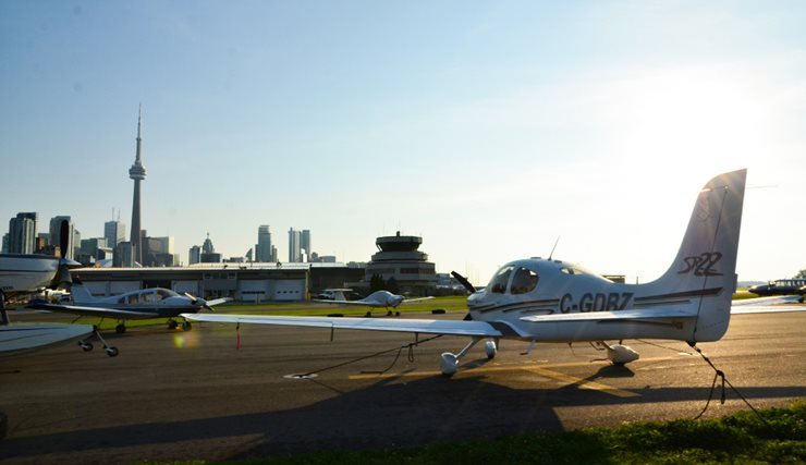Modern photo of private planes on the runway with downtown Toronto in the background