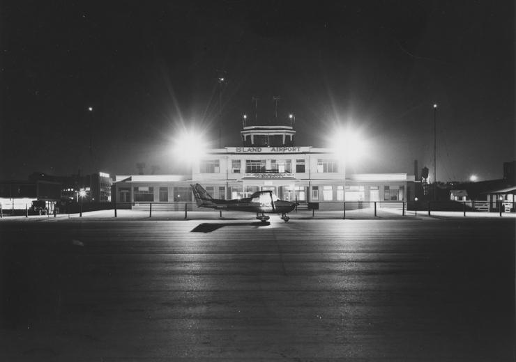 Prop plane infront of terminal at night