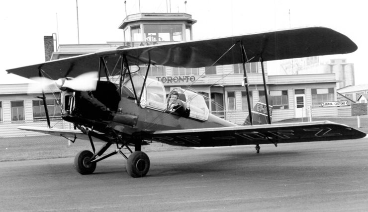 Early to mid-1900's aircraft on the runway infront of old terminal A