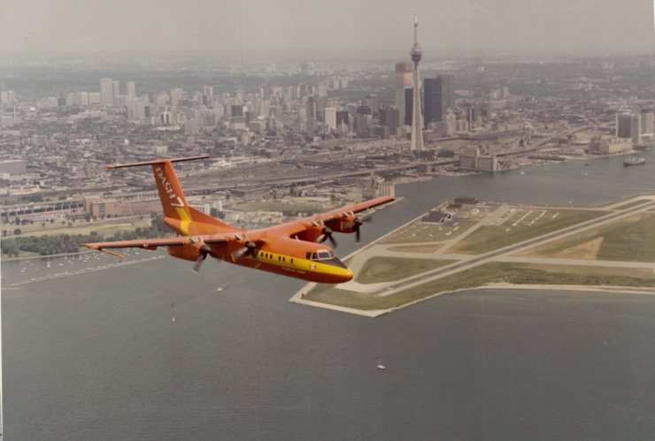 Aircraft in foreground aerial photograph with downtown Toronto and the Billy Bishop Airport in the distance